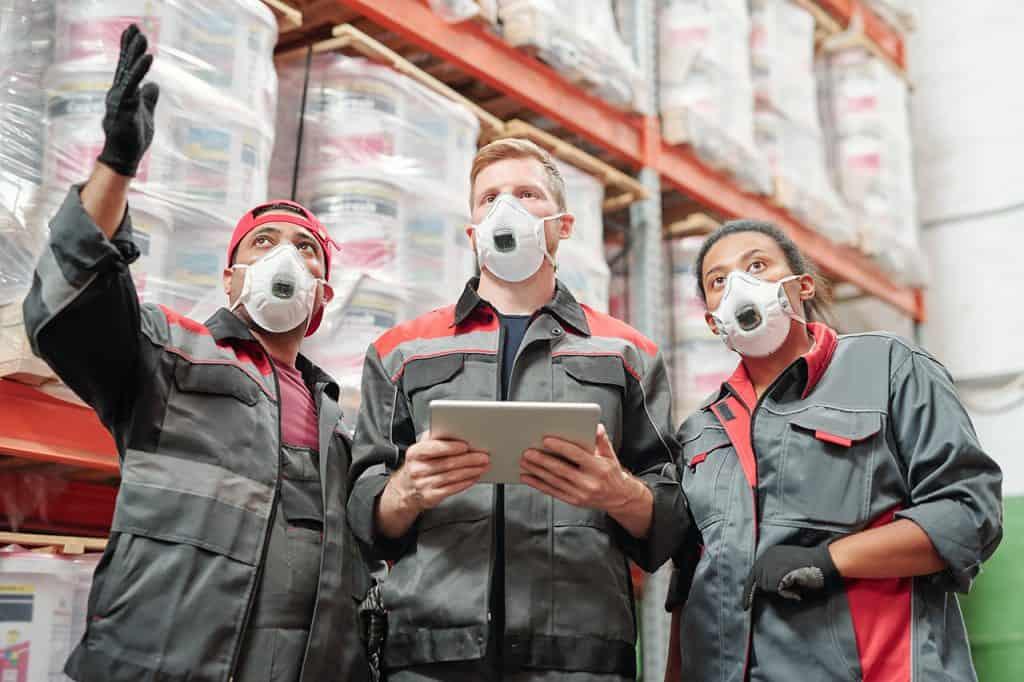 Jóvenes trabajadores de almacenes mascarilla de protección contra el coronavirus